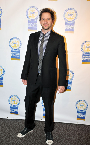 Jamie Kennedy successfully mixed print on print by wearing a checkered polo shirt with a stylish gray striped tie.