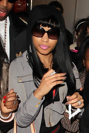 Nicki Minaj covered up at Heathrow Airport in black oversize sunglasses.