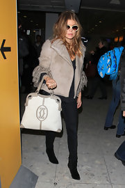 A jet setting Fergie carried a white and taupe Marcello de Cartier shopping bag. The standout purse complemented her cream fur coat.