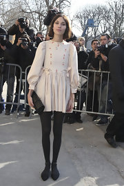 Alexa Chung carried a black quilted roll clutch to the Chanel fashion show.