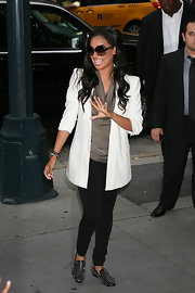 La La paired her studded loafers and black tights with a white blazer.