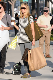 Heidi Klum kept her look decidedly casual, teaming an oversize striped shirt with a studded olive canvas tote.