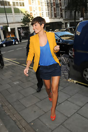 Frankie Sandford added major color to her stylish street wear with a pair of orange suede peep-toes.