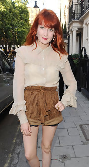 Florence wears a nude ruffled button-down blouse with high-waisted suede shorts in Mayfair, London.