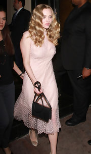 Amanda Seyfried contrasted her girlish pink dress with a black leather shoulder bag.