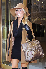 Gretchen dons a camel cape over a turtleneck dress and paired with a matching floppy JLo hat.