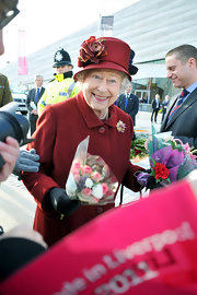 Queen Elizabeth II perfectly matched her maroon winter coat to her decorative floral hat while visiting Liverpool.