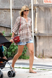 Heidi Klum paired her plaid shirt with a red shoulder bag.