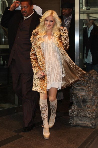 The reality starlet wore a pricey pair of gold sequin-embellished knee-high socks with laced-up Louboutin booties and a gold coat.