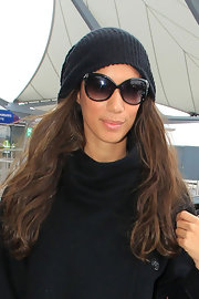 Leona rocks a knit beanie with large black sunglasses.