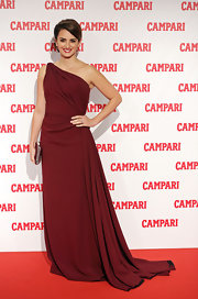 Penelope wore this rich burgundy gown with a side train for her exquisite Milan look.