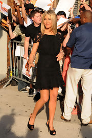 Jennifer Aniston complemented her flirty black lace dress with a pair of matching black patent bow peep-toes.