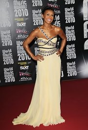 Melody wore a pale yellow chiffon evening gown with bold black detailing on the bodice and a single shoulder strap.