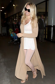 Pamela Anderson arrived at LAX wearing an ensemble of soft neutrals that included a pair of tan heeled sandals.