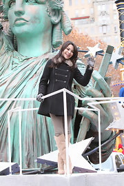 Miranda waves for the Macy's parade in a black military style wool coat with a faux fur collar.