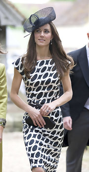 Kate wore a black decorative hat with her print sheath dress for a wedding with her sister, Pippa.