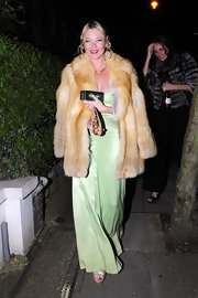 Kate channels 70's glamour in a sage green silk evening gown and fur coat.