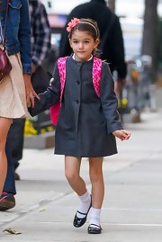 Suri looked adorable in this classic grey pea coat, especially with her bright pink backpack in tow.