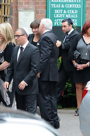 Alex Winehouse attended his sister's funeral in a classic dark suit.