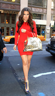 Khloe donned a curve-hugging orange body-con dress which she topped off with a pair of Louboutins, which she paired with an awesome metallic gold tote bag.