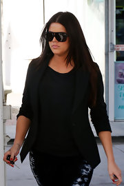 "Khloe shields her self form the paparazzi with her blacked out ""Fez"" sunglasses."