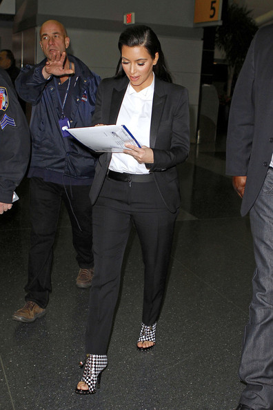 Kim Kardashian signs autographs while she makes her way through a terminal in JFK airport to catch a flight out of New York City