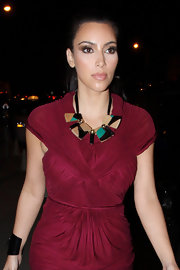 Kim Kardashian outfitted her ruched burgundy dress with a bold tribal-inspired necklace.