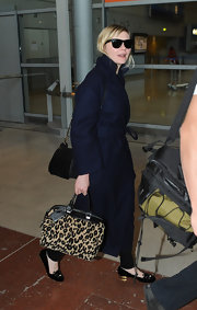 Kirsten Dunst opted for a cool and glamorous travel look while flying into Paris when she opted for a navy wool coat and leopard bag.