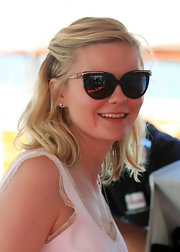 Kirsten Dunst looked glam in black cateye sunglasses with gold floral ear pieces.