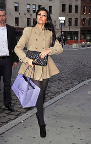 Kourtney K. kept warm in NYC in a tan double breasted coat paired with black suede ankle boots.