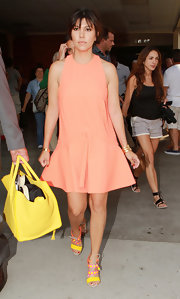 Kourtney kept her travel look casual but fun with this sleeveless peach shift dress.