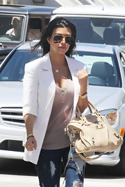 Kourtney wore gold accessories including a pricey gold watch that's known as the ultimate status symbol of watches-the Rolex.