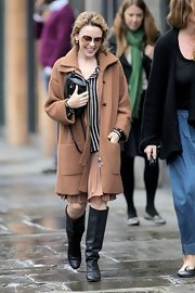 Kylie Minogue completed her cozy neutral look with classic knee-high black boots.