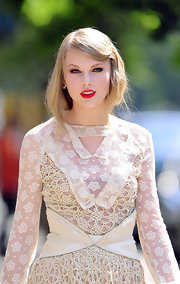 To recreate Taylor Swift's faux bob, allow straight hair to dry naturally amd brush thoroughly with a natural bristle brush. Next, spritz with a product like Bumble and Bumble Does It All spray, create a deep side part and add a decorative barrette. Finally, pull hair back into a very loose, low ponytail, twist under and pin into place.
