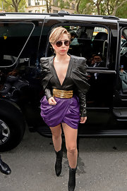 Lady Gaga chose a black leather, draped and pleated top to pair with a grape-hued draped mini skirt.