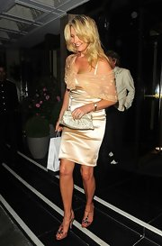 Penny Lancaster teamed up her gold dress with a woven metallic purse.
