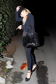 While making another odd appearance, Lindsay Lohan is seen wandering outside a Hollywood home. Well at least she was carrying a cute patent leather bag.