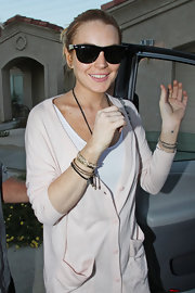 A content looking Lindsay Lohan shields her eyes from the paparazzi in oversize Ray-Ban wayfarers.
