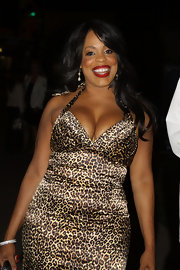 Niecy is stylish in long curled waves with side-swept bangs.
