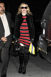 "The pop star sported an interesting look for a 51-year-old mother complete with a striped Louis Vuitton dress and the black leather ""28 bag""."