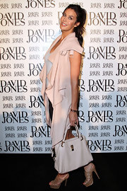 Megan Gale paired a white leather tote with a draped coat for a stylish finish at the David Jones spring/summer season launch.