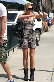 While out with boyfriend Liam, Miley paired her leopard print dress with a leather shoulder bag.