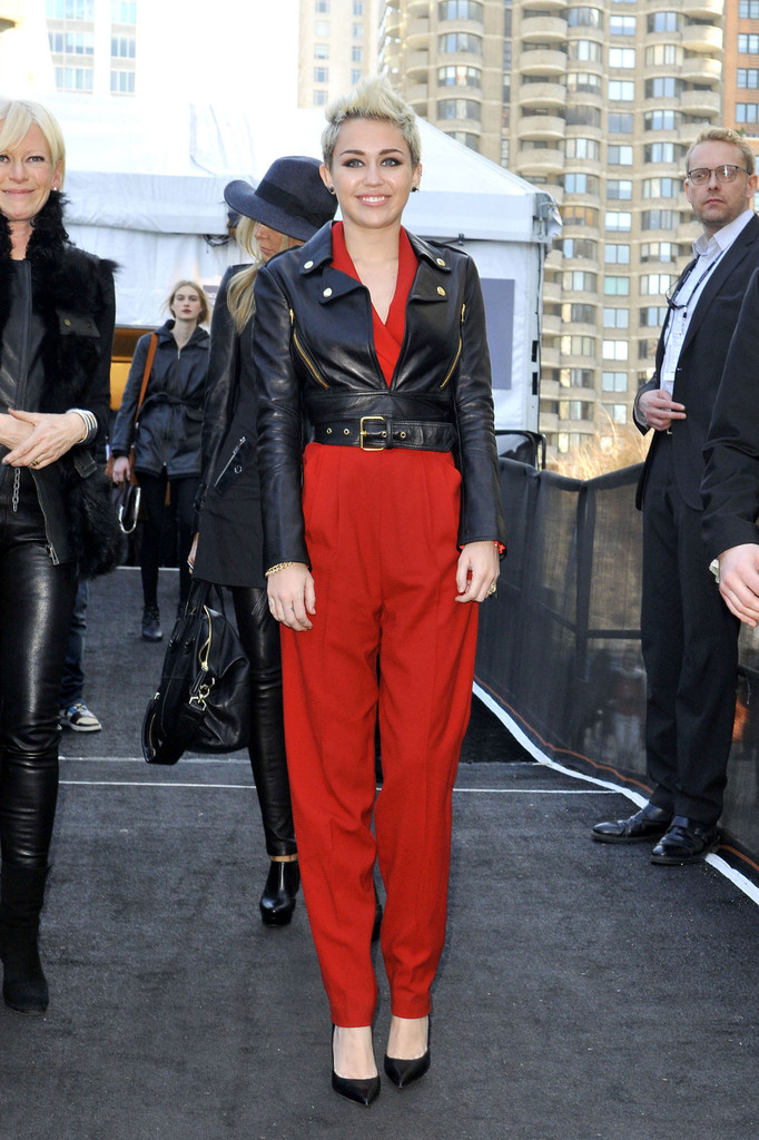 Miley Cyrus sports a bright red romper suit as she attends the Rachel Zoe Fall 2013 Show during New York Fashion Week