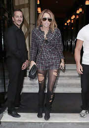 Miley Cyrus wore ripped leggings with a plaid shirt while out and about in Paris.