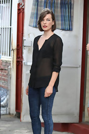 Milla's sheer black button down revealed just a peek of skin on set of 'Cymbeline.'