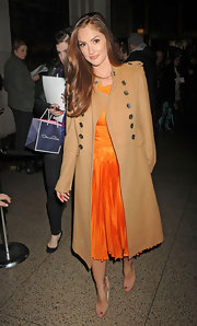 Minka Kelly accessorized her bright pleated orange dress with nude peep-toe pumps.