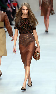 Cara Delevingne held a metal studded leather hobo bag on the Burberry LFW runway.