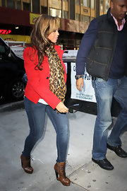 Beyonce was spotted in a chic red coat accessorized with brown leather lace-up boots.