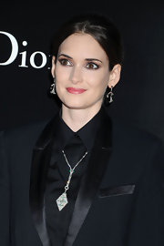 Winona added a subtle touch to her black suit with a pendant necklace.