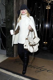Kristen Bell paired a winter white cape with a luxe white leather tote with brown piping.